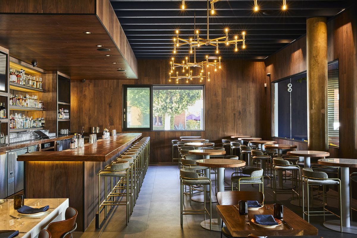 A wood-lined restaurant interior, complete with bar-top tables and low lights.