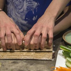 Vegan chef Molly Aubuchon, of Kent, Ohio,  helps her son Sam, 11,  learn to roll maki rolls while the two make vegan sushi together for dinner.