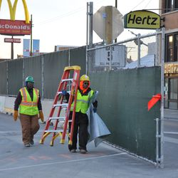 They may have been measuring the top of the gates to add more of the decorative tarp