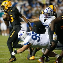 Arizona State quarterback Jayden Daniels, left, runs past the BYU defense as Brigham Young defensive lineman Caden Haws (95) tackles during an NCAA college football game at LaVell Edwards Stadium in Provo on Saturday, Sept. 18, 2021.