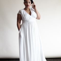 A classic, empire-waist meets a plunging v-neckline with this gown. It also has a scalloped back and lace cap sleeves.