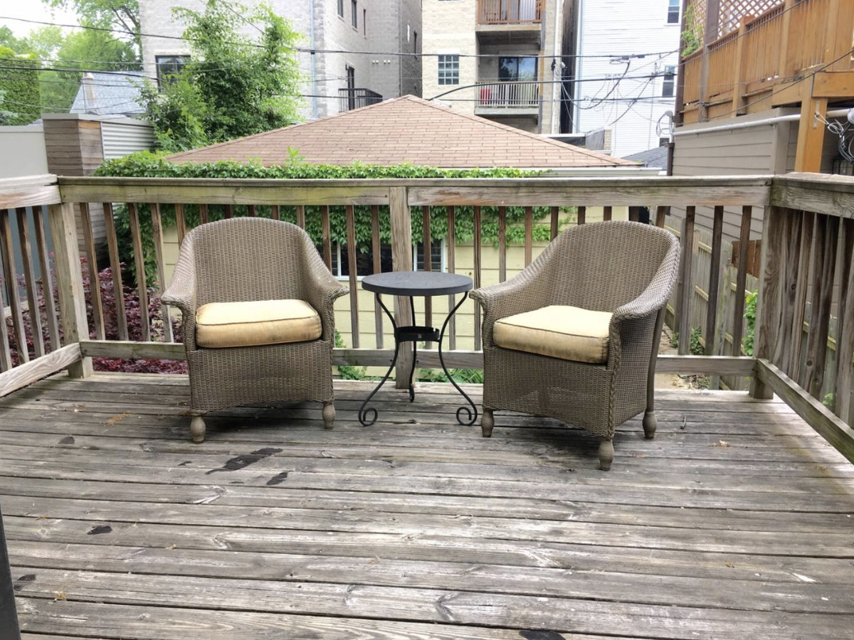 A view of the back deck with wicker chairs and a small backyard.