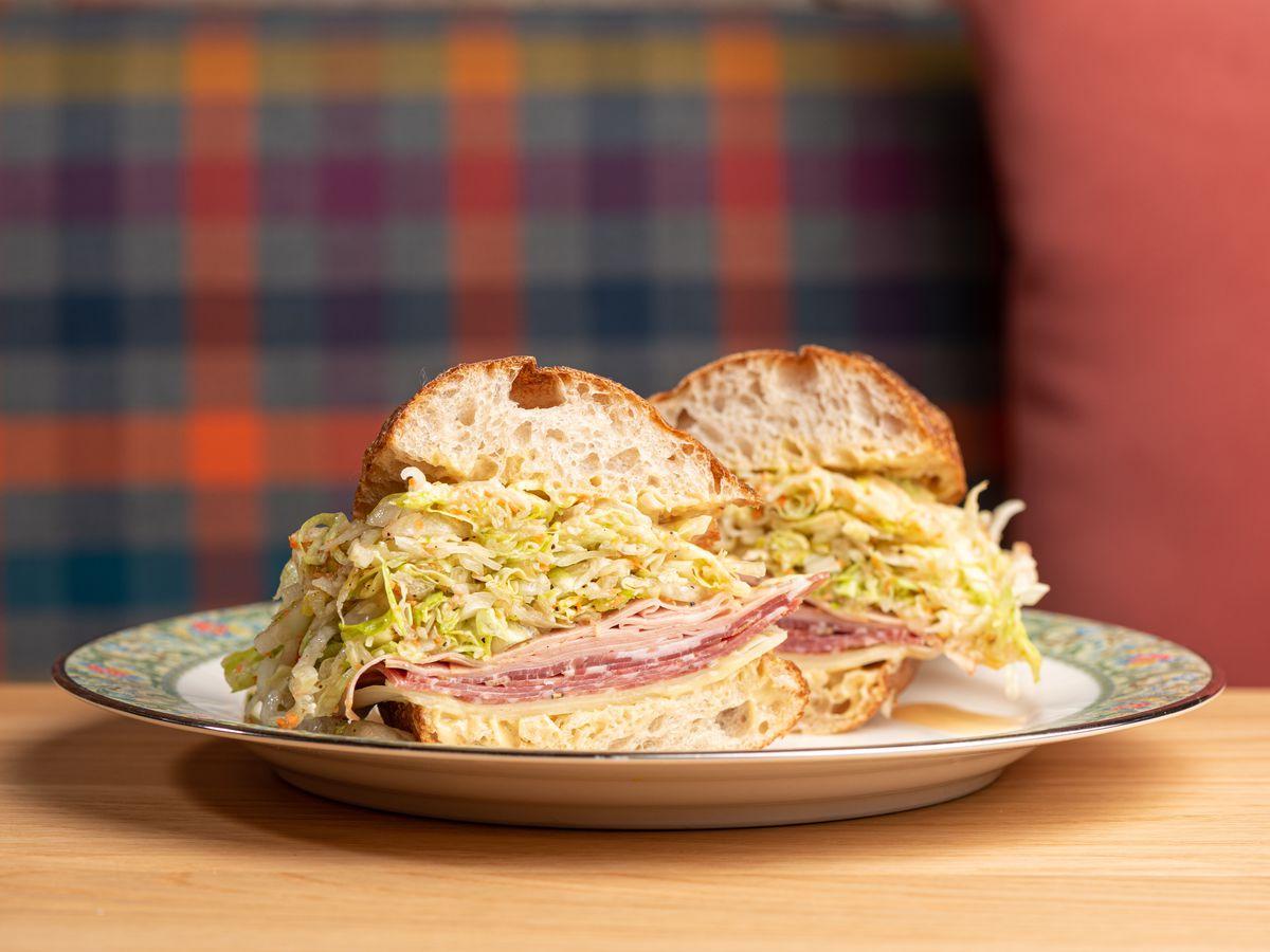 An Italian style cold cut sandwich shown cut in half with a plaid backgrounhd.
