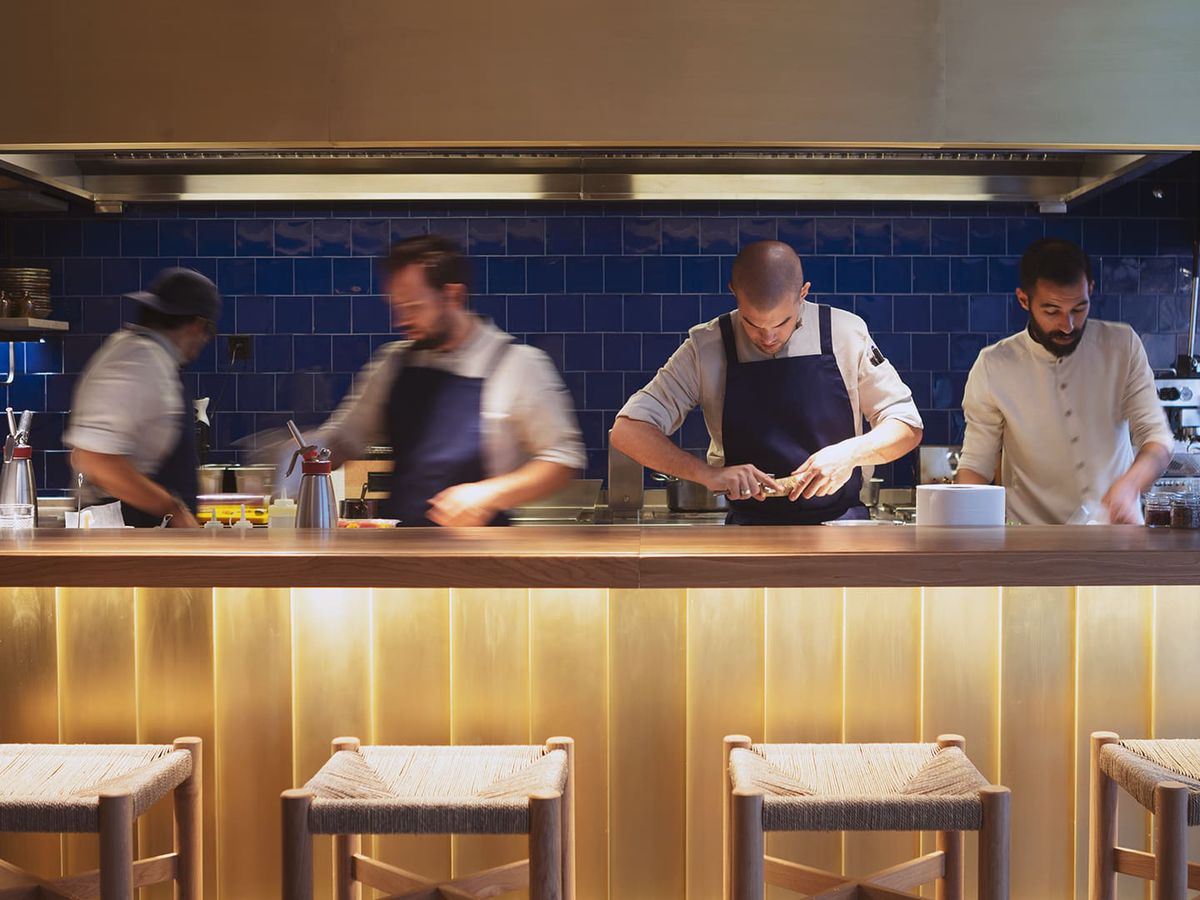 A kitchen counter with four restaurant team members working behind it and four empty stools arranged in front.