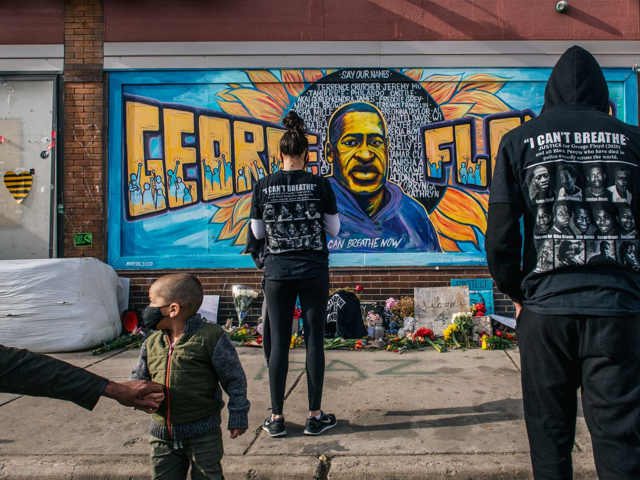 People pay their respects Tuesday at the mural of George Floyd in Minneapolis following the guilty verdicts in the Derek Chauvin trial.