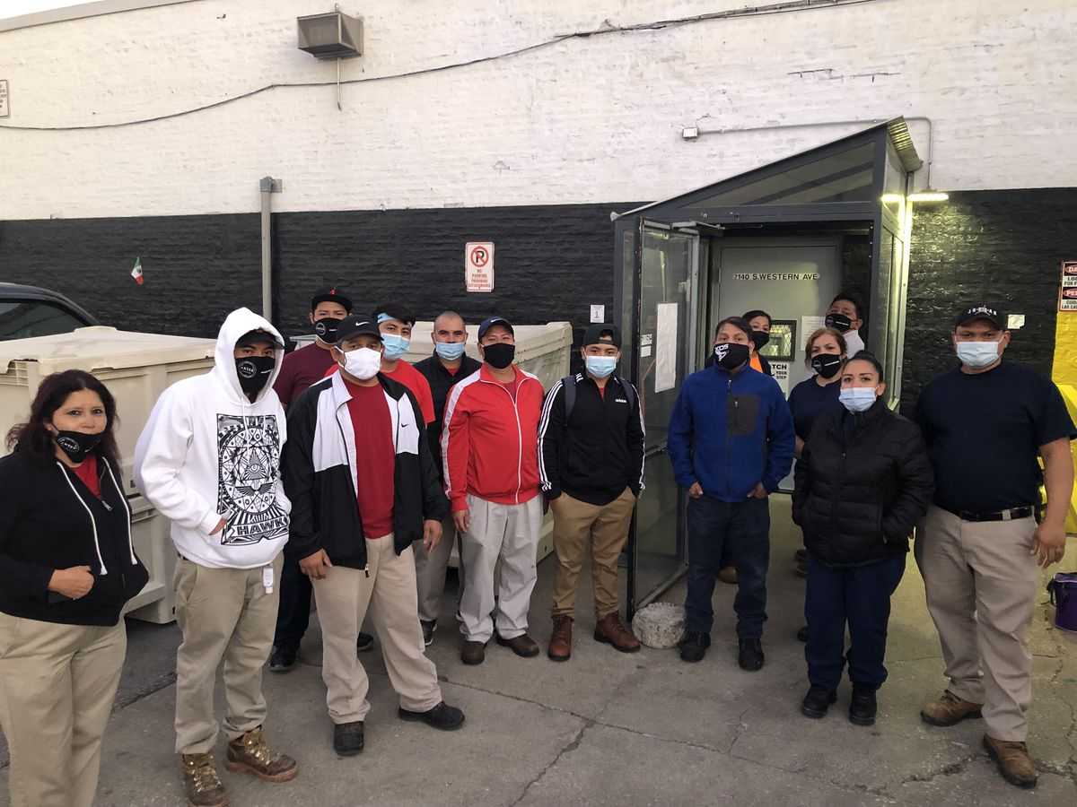 a group of factory workers wearing face masks standing outside their workplace