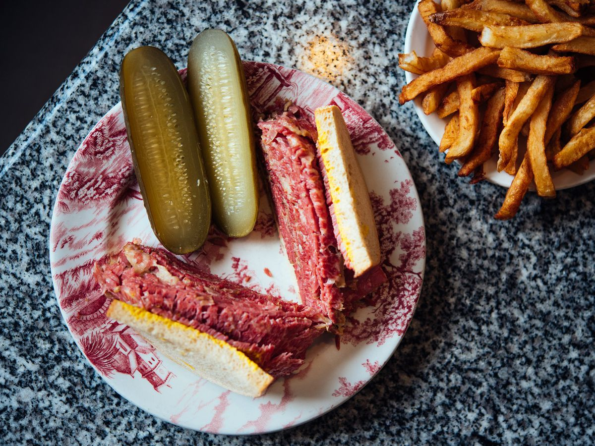 A smoked meat sandwich on a plate next to pickle halves, with a bowl fo fries next to it.