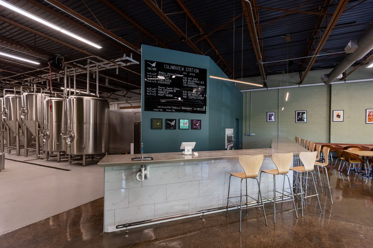 The bar at Brewery Faisan is made from white marble tiles with a concrete top. light wood bar chairs line the bar and a blue wall behind the bar is a backdrop to the black and white beer menu.