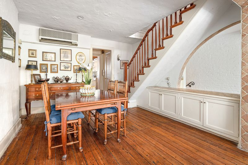 A dining area with hardwood floors, a dining table, four chairs, white walls, and a wooden staircase in the back.