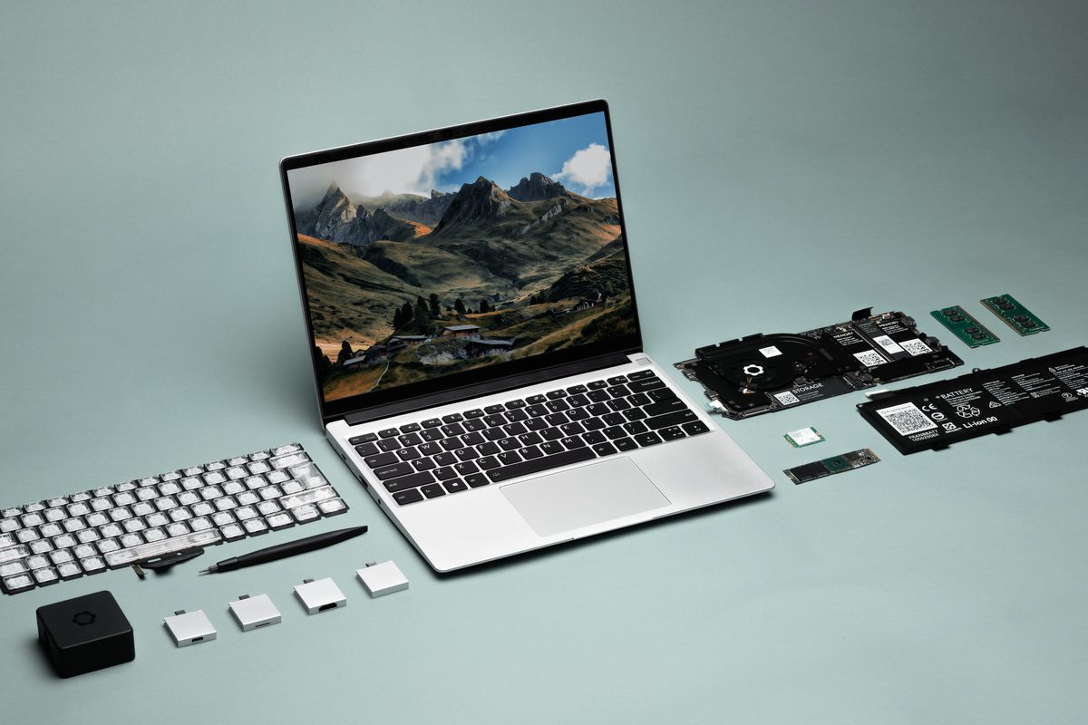 A Framework Laptop angled slightly to the right, seen from above. The screen displays mountains and a valley. On either side are a number of modules.
