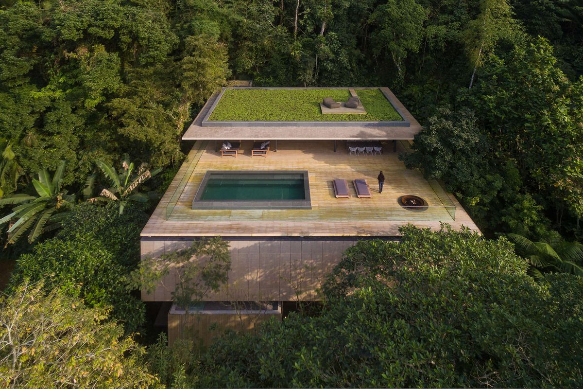 A boxy concrete home with green roof and a large floor jutting out from underneath with pool on deck nestled deep into the rain forest.
