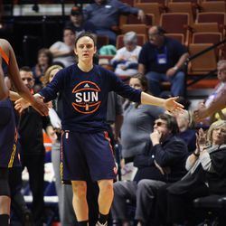Former Husky and Connecticut Sun's Kelly Faris (34) greets her teammates at a break in the action.