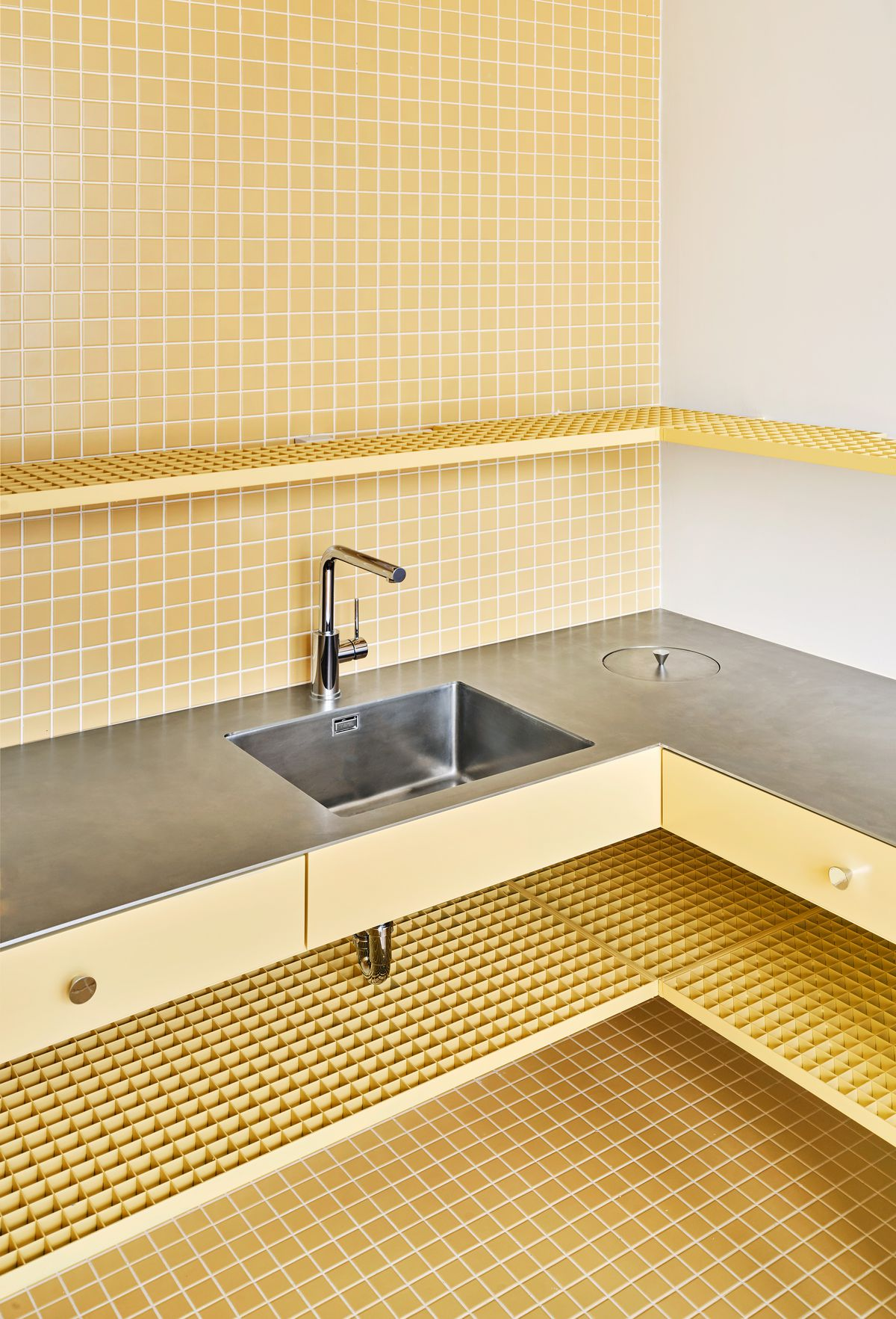 Kitchen with yellow tile and drawers and metal sink and counters.