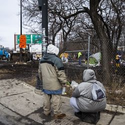 People sit on the curb and watch as workers from the city's Department of Streets and Sanitation clears out a homeless encampment near South Desplaines Street and West Roosevelt Road, Monday morning, Feb. 10, 2020.