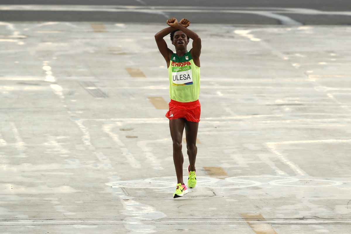 Feyisa Lilesa of Ethiopia crossed both arms in an X abve his head as he wins silver during the Men's Marathon on Day 16 of the Rio 2016 Olympic Games.