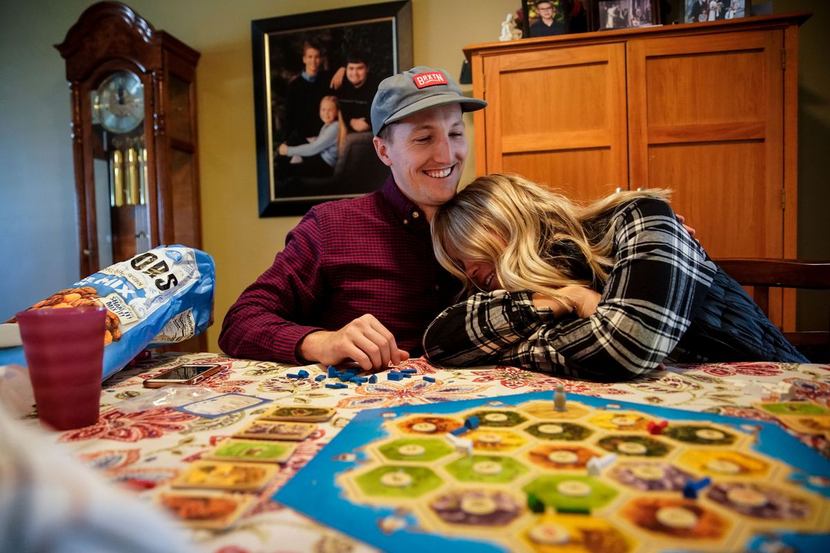 Brookston Jeppso hugs wife Haley while playing a board game at his parents' house in Salt Lake City on Sunday, Oct. 3, 2021. The new edition of the American Family Survey examines relationship quality and attitudes about marriage, among other topics.