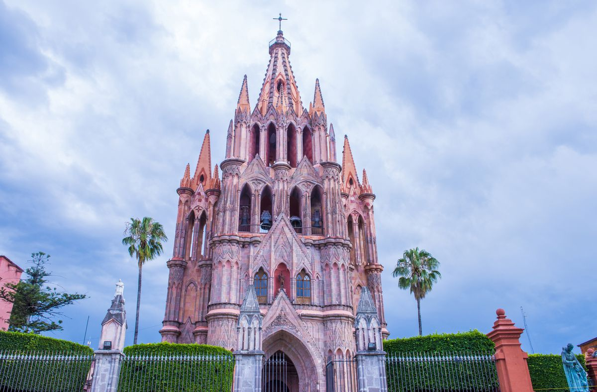 """The exterior of <span data-author=""""843"""">Parroquia de San Miguel Arcangel church in Mexico. The facade is pink and there are multiple towers.</span>"""