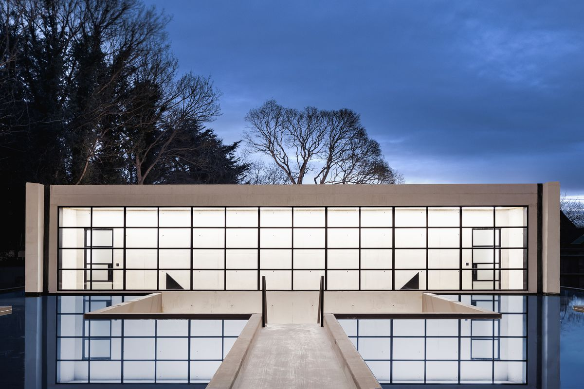 Concrete house with glass windows glowing at night.