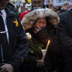 A woman cries as hundreds of mourners gather for a vigil in a parking lot in the 2000 block of South Wells in Chinatown, where Huayi Bian and Weizhong Xiong were shot to death, Wednesday, Feb. 12, 2020. Bian and Xiong were killed during an apparent robbery, for which Alvin Thomas faces two counts of first-degree murder.