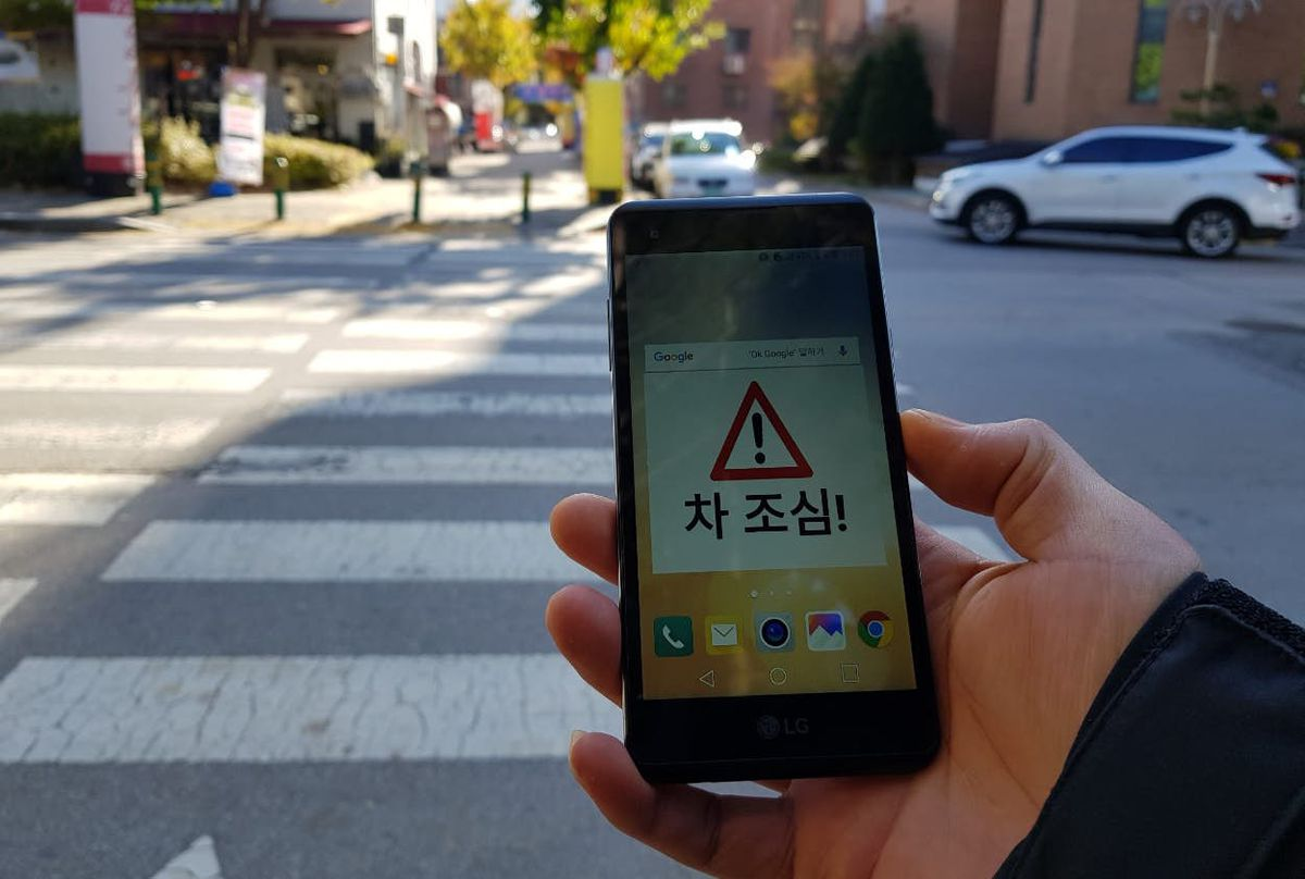 Person holding app with warning signal on screen