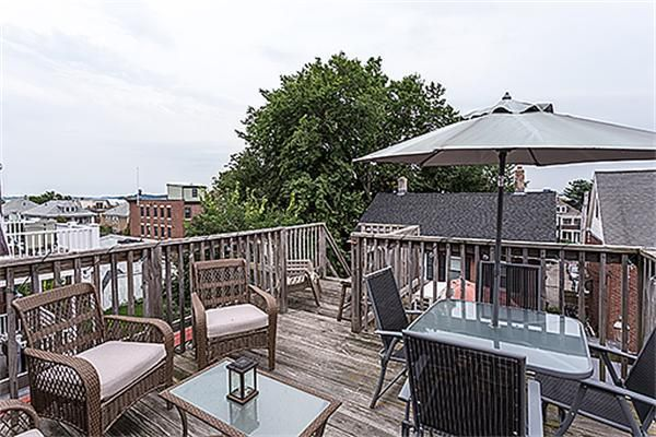 A roof deck with furniture, including an opened umbrella.
