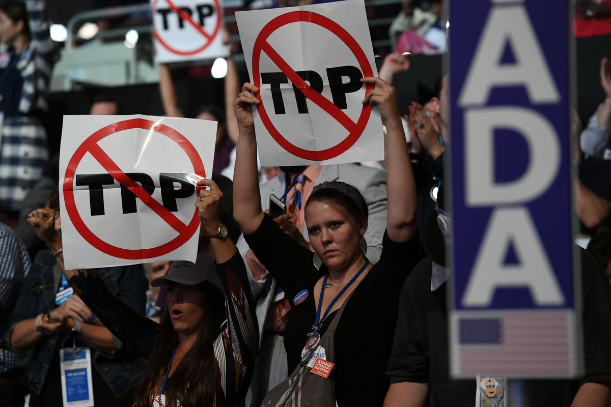 Protesters in 2016 hold up signs representing TPP, the Trans-Pacific Partnership, with a circle and a line across it.