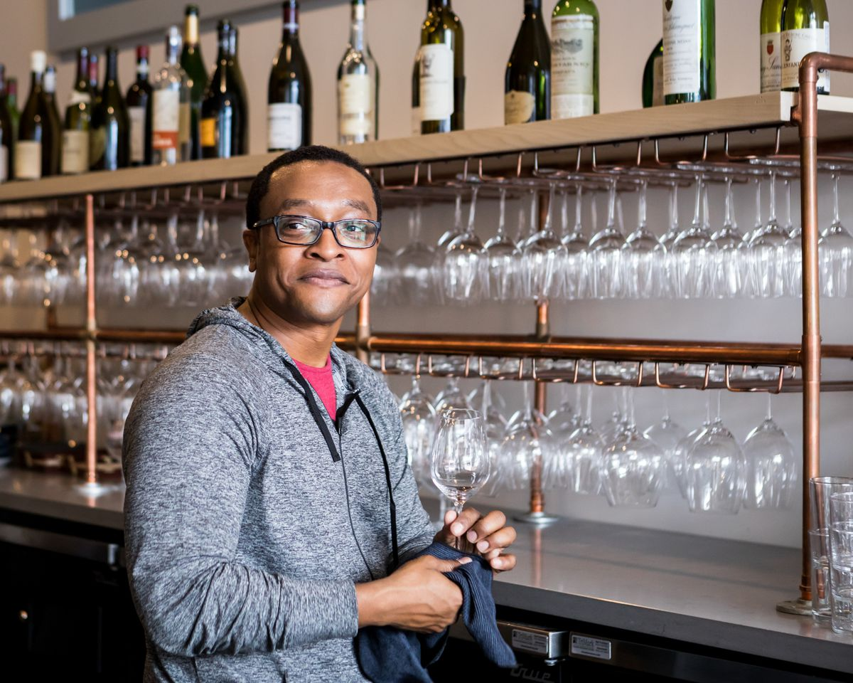 A bartender polishes a wine glass and looks over his shoulder, smiling.