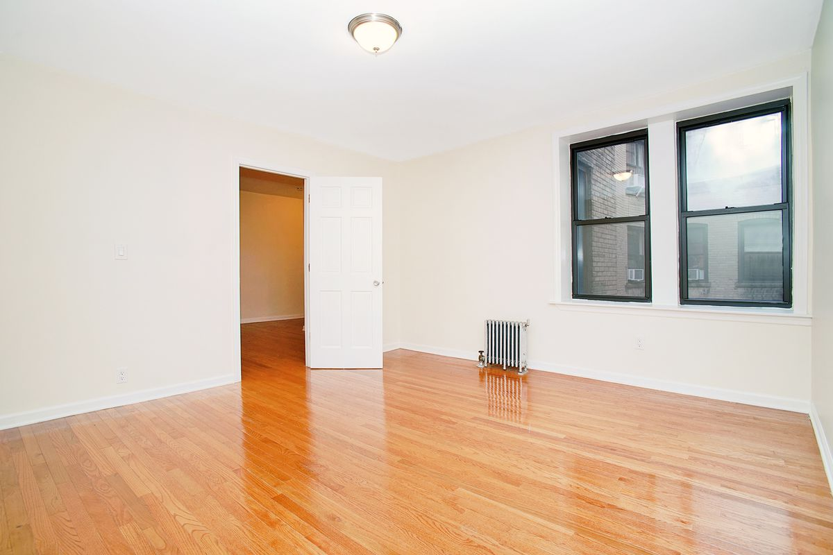 A room with two windows, base moldings, beige walls, and hardwood floors.