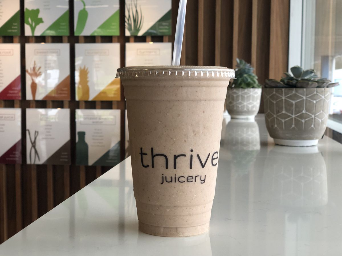 A brown smoothie in a plastic Thrive Juicery cup sits on a white counter with succulents in the background.