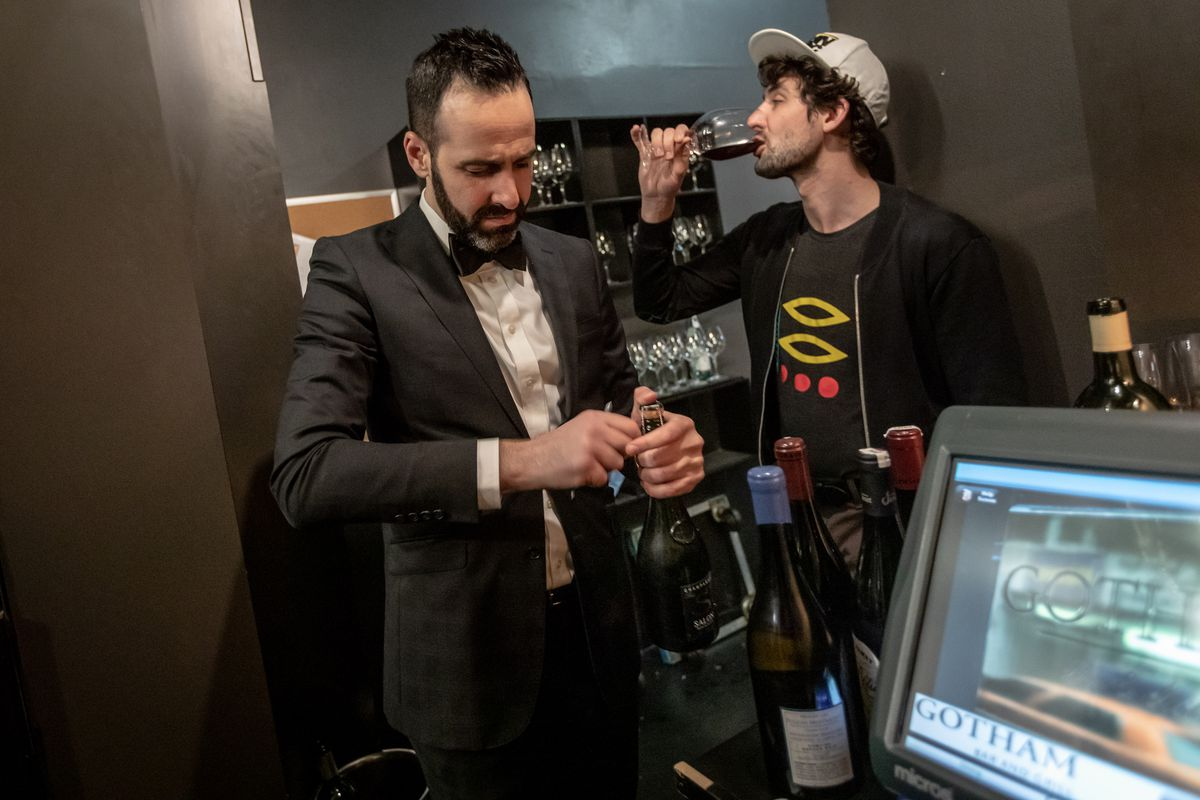 Wine director Josh Lit, wearing a suit, opens a bottle of Champagne, as a man drinks a glass.