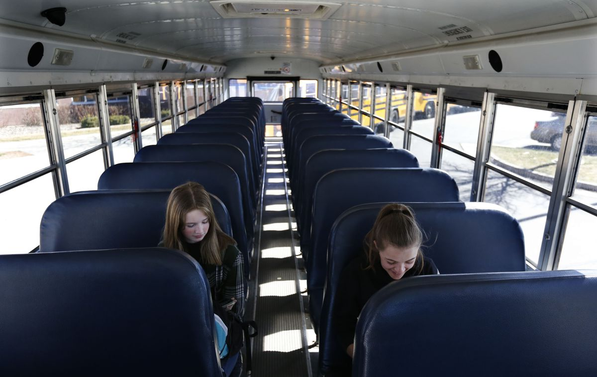 Sophomores Zoe Scott and Oakleigh Harman wait for their bus to leave Murray High School on Thursday, March 12, 2020. Murray City School District announced Thursday it is closing its schools until further notice amid spread of the novel coronavirus in Utah. Most students and teachers left school after the announcement was made earlier in the day.