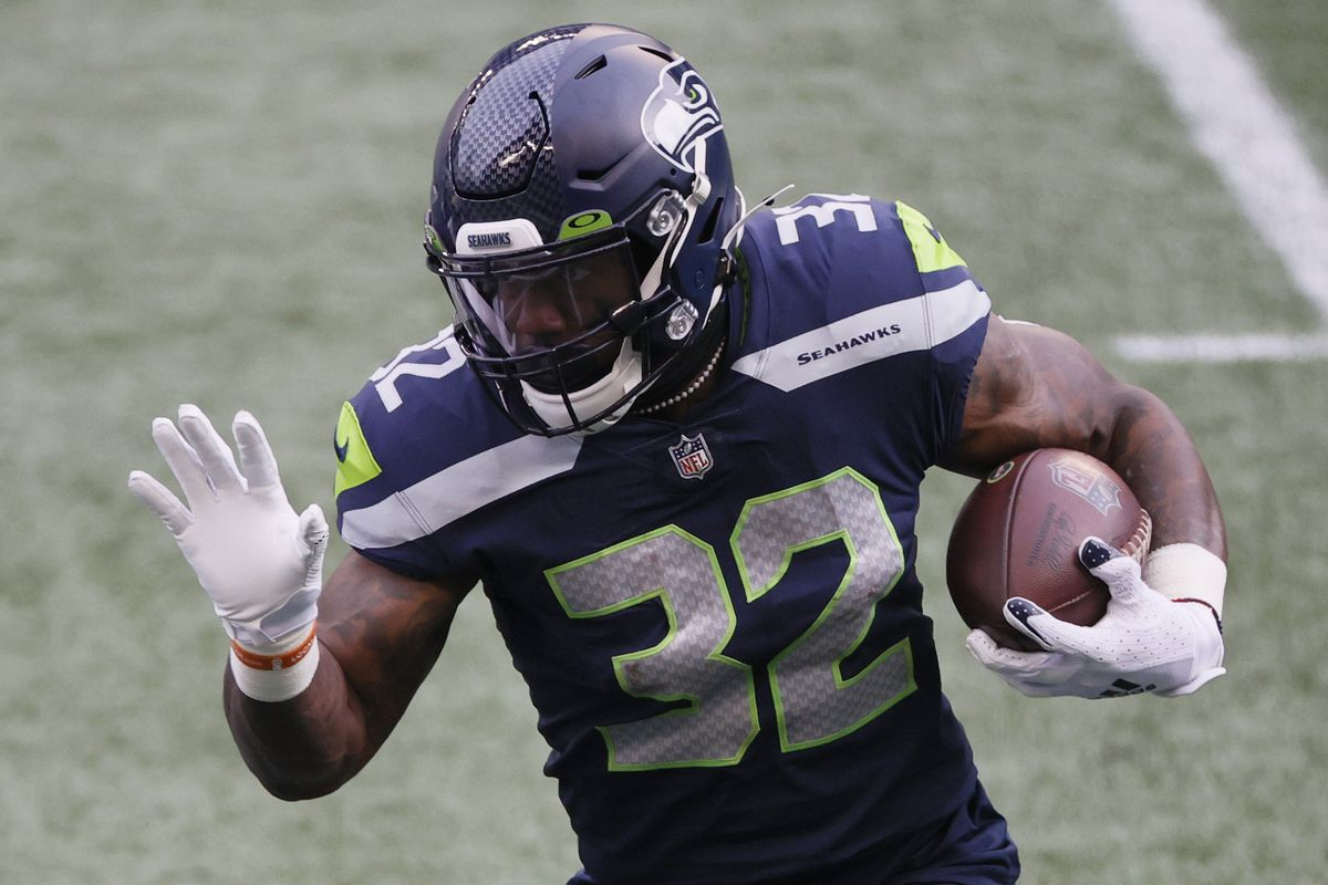 Running back Chris Carson #32 of the Seattle Seahawks carries the football against the defense of the Los Angeles Rams during the first quarter of the NFC Wild Card Playoff game at Lumen Field on January 09, 2021 in Seattle, Washington.
