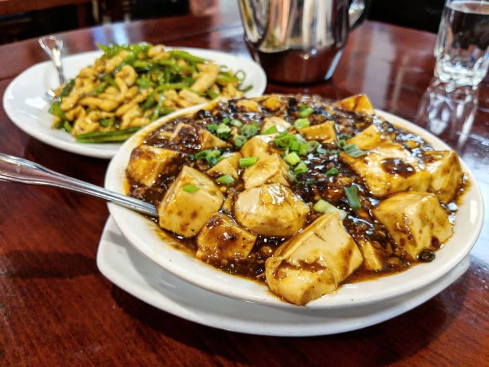 A ma po tofu dish sits on a wooden table at a restaurant