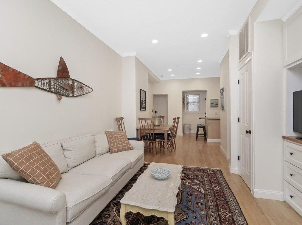 A long, narrow living room-dining room with furniture, and there's a kitchen at the end.