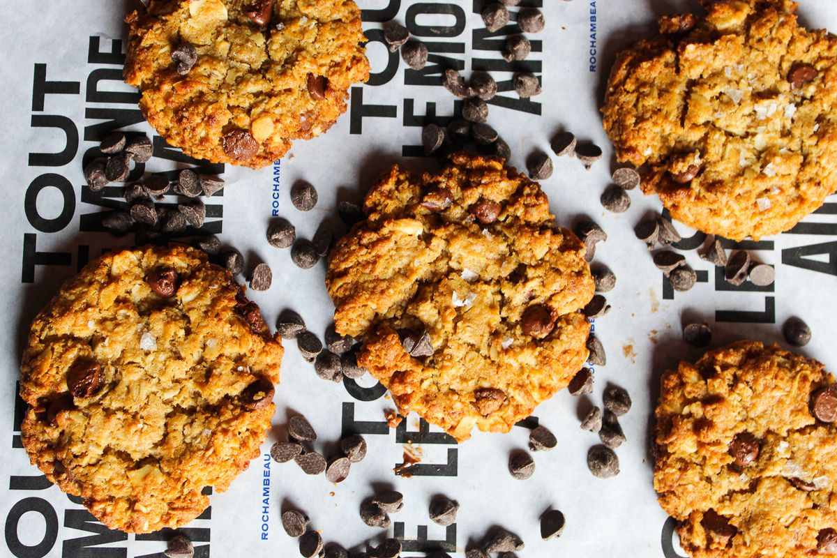 Five chocolate chip cookies sit atop patterned paper with chocolate chips sprinkled in between