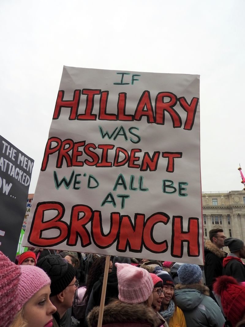 """A woman carries a sign at a Women's March, which reads: """"If Hillary was president, we'd all be at brunch."""""""