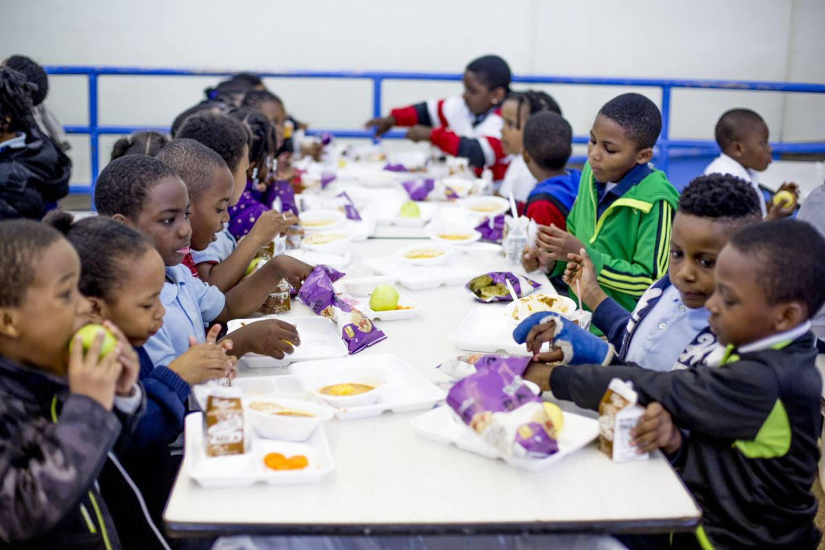 Young children sit at a long white table and eat lunch in a school cafeteria.