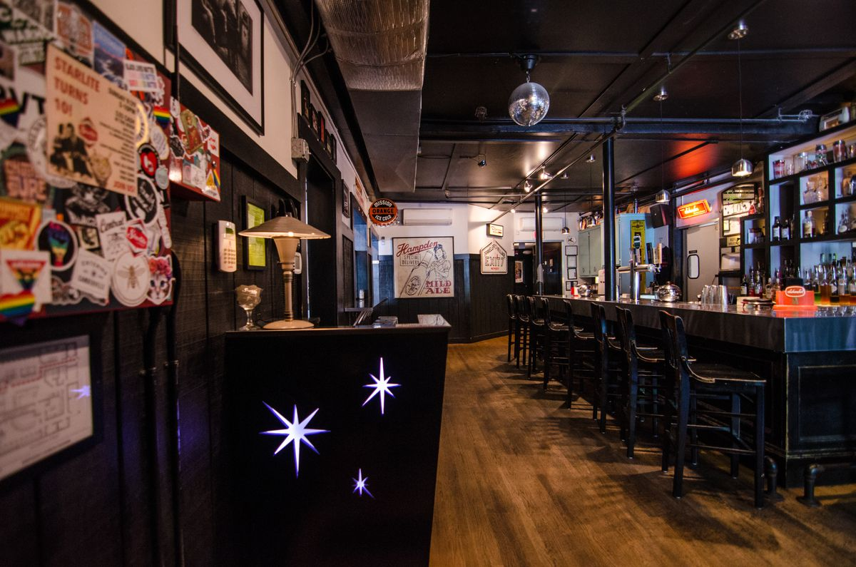 A view into a bar, starting with a star-spangled host stand. A disco ball hangs from the ceiling.
