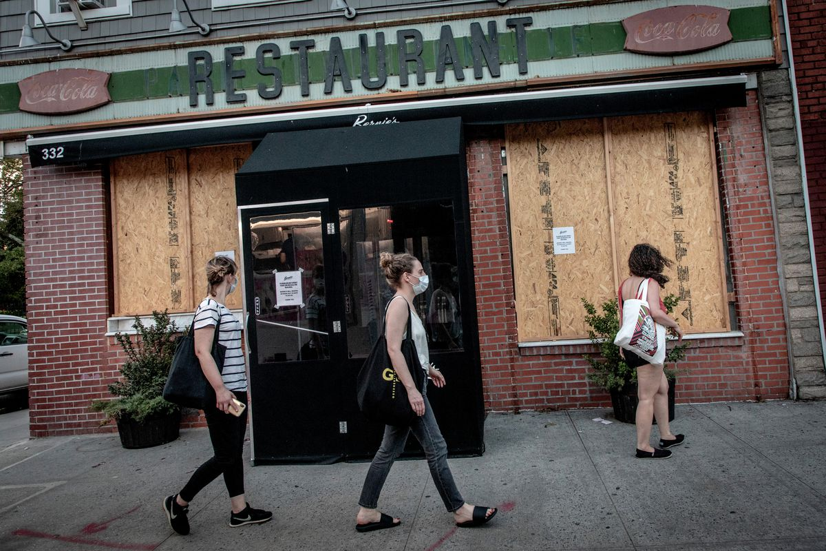 Three people walk outside a boarded up restaurant