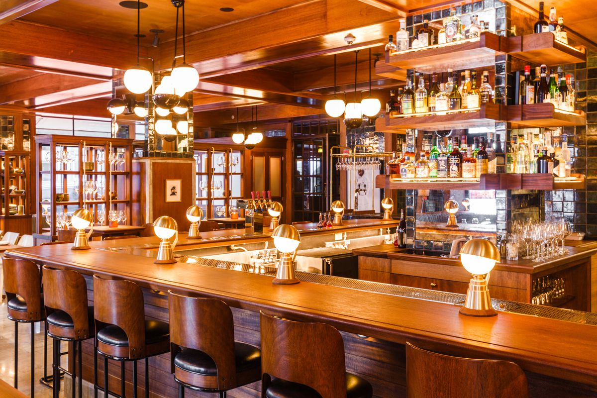 A view of Simon & the Whale's shiny wooden bar with Art Deco lighting and shelves lined with bottles of liquor.