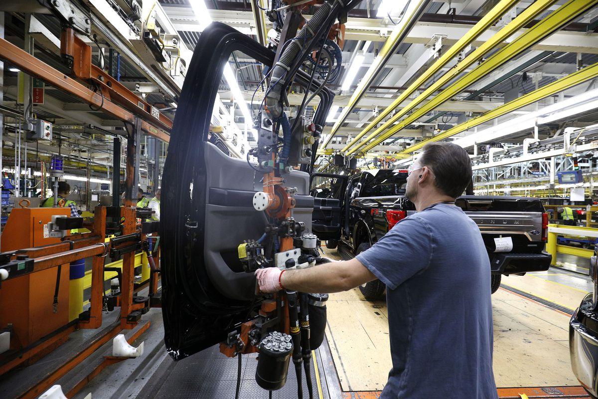 Inside a car factory, where a worker is assembling the door of a truck.