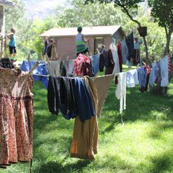 Freshly washed laundry hangs on a line outside John Rowe Moyle's old house at Moyle Park in July 2014. In the background kids are dancing and playing on stilts, things pioneer children used to do for fun.