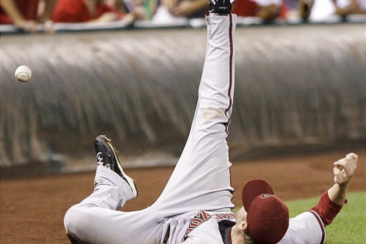 Arizona's Mark Reynolds tumbles after trying to catch a pop fly foul on Wednesday.