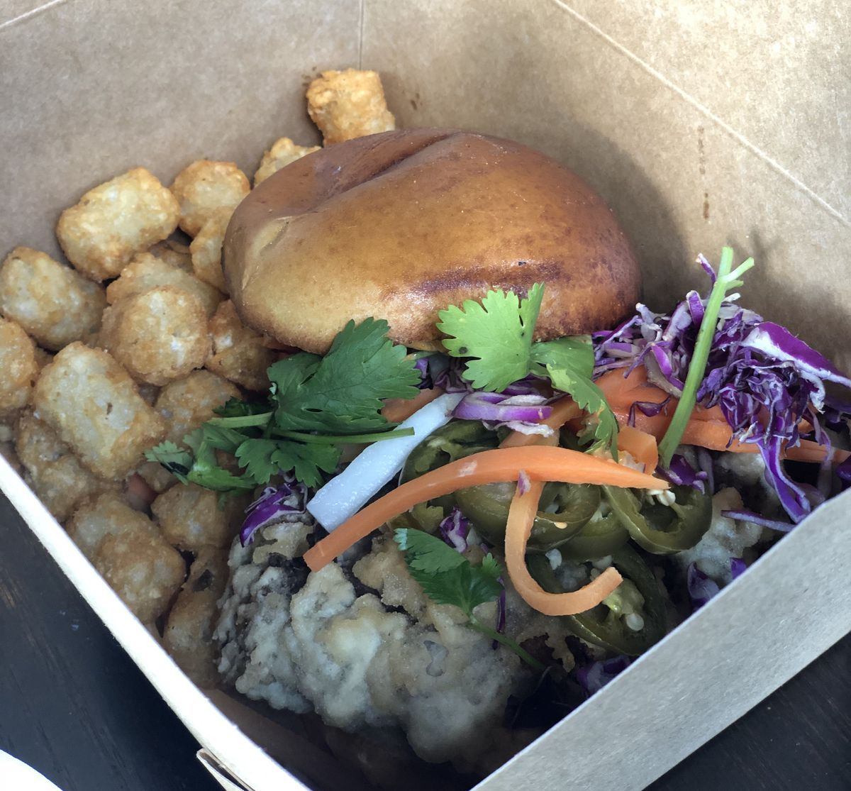 A mound of tater tots balances next to a brioche bun, jalapeno, cabbage, shredded carrot, and other toppings in a takeout container