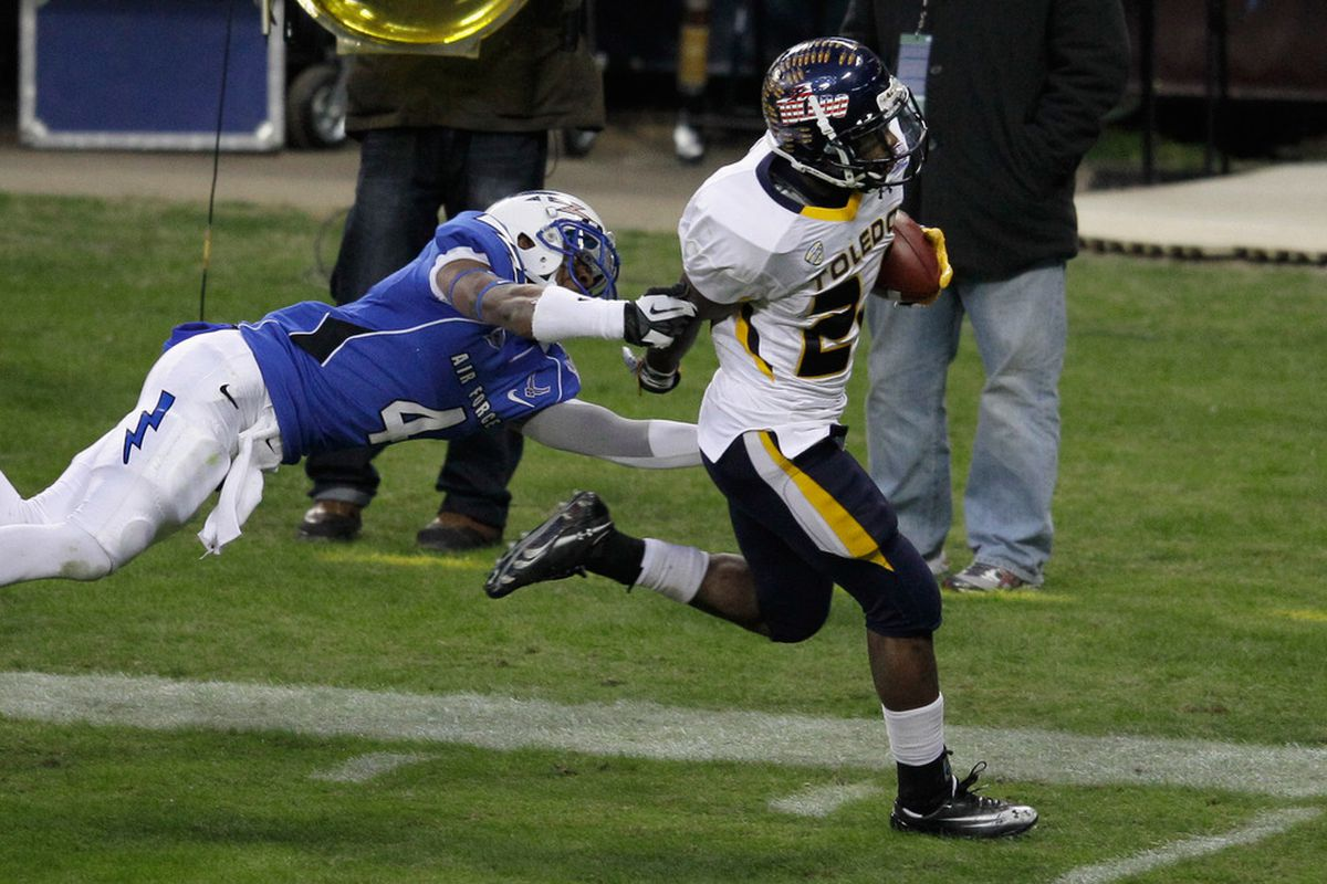 Adonis Thomas #24 of the Toledo Rockets breaks the tackle of Anthony Wooding Jr. #4 of the Air Force Falcons for a rushing touchdown during the first half of the Military Bowl at RFK Stadium.
