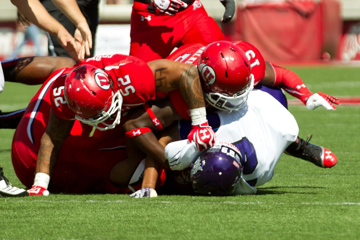 Utah Utes linebacker V.J. Fehoko (52) and defensive back Michael Walker (15) tackle Weber State Wildcats running back Zach Smith (29) during the first quarter at Rice-Eccles Stadium.