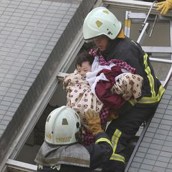 A child is rescued from a toppled building after a 6.4-magnitude earthquake in Tainan, Taiwan, Saturday, Feb. 6, 2016. The earthquake struck southern Taiwan early Saturday, toppling at least one high-rise residential building and trapping people inside. (AP Photo)