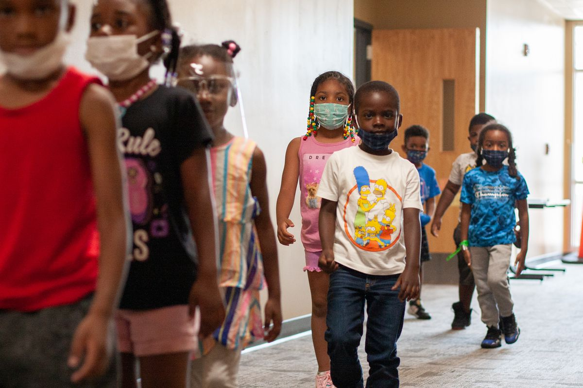 A group of kindergarten students with masks on walk down the hall in a line