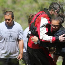 A member of the Search and Rescue team hugs a relative of a 22-year-old hiker who fell in Bell Canyon as crews work to recover the body on Monday, June 5, 2017. Siaosi Brown's body was spotted in the lower falls of the canyon. His body was trapped on some logs in the middle of the waterfall, Unified Police Lt. Brian Lohrke said.