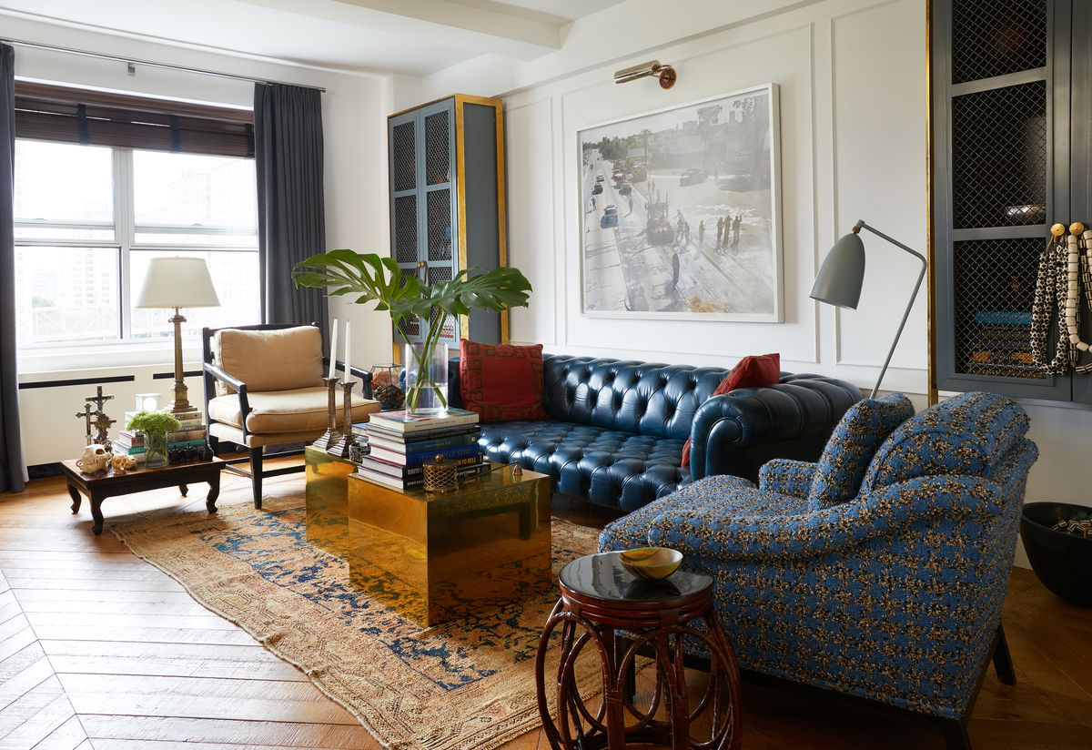 A living room. There is a dark blue leather couch, a patterned blue arm chair, and a tan armchair. A yellow patterned area rug sits under a metallic gold coffee table. There are stacks of books and a houseplant in a planter on the coffee table. A large wo